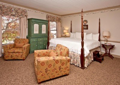 Four post bed in room with wallpaper, green armoire and two chairs