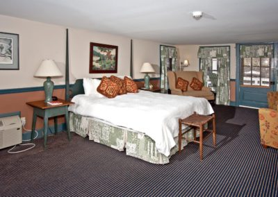 Room with white antique bed and striped carpet