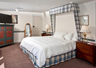 Room with curtains behind bedframe, flatscreen TV and antiques