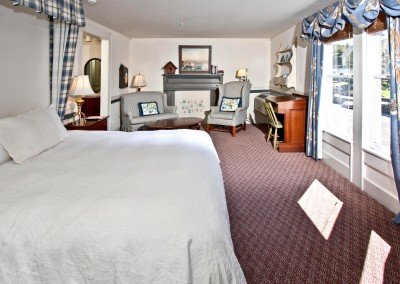 Room with red carpet, windows, desk and antique furniture