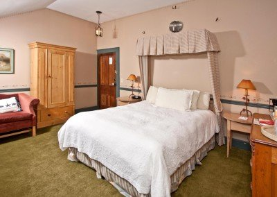 Curtains behind bed in room with pine armoire